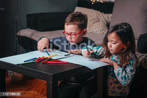 983418152 istock photo Cheerful little children having fun doing finger painting 1131189132