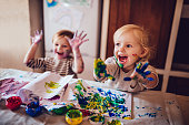 Happy little girls with dirty hands and faces having fun being creative with finger painting