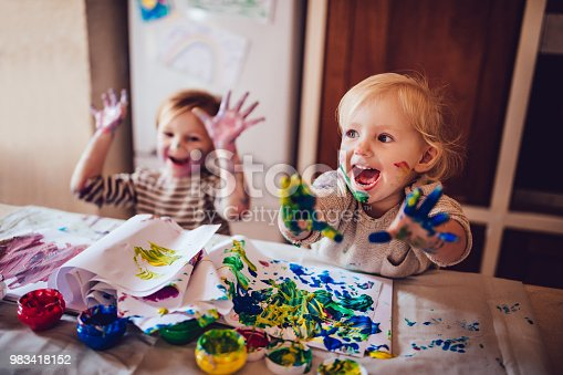 983418152 istock photo Cheerful little children having fun doing finger painting 983418152