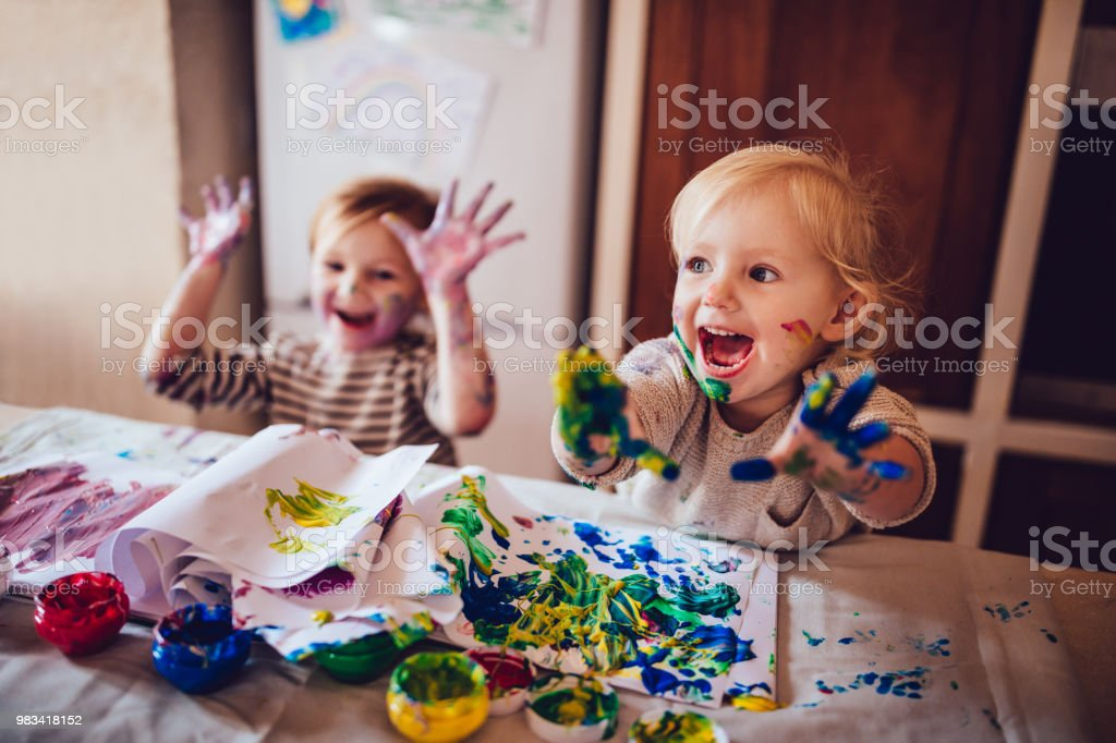 Cheerful little children having fun doing finger painting stock photo