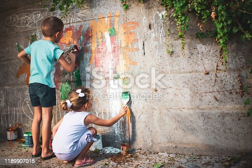 983418152 istock photo Cheerful little children having fun painting wall 1189907015