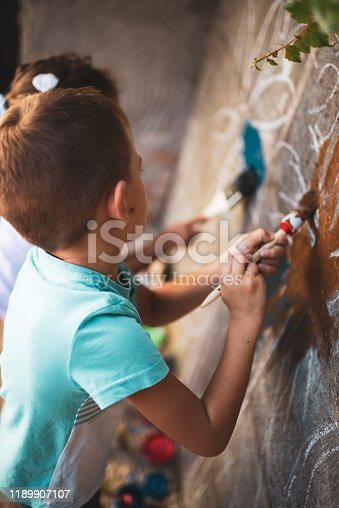 983418152 istock photo Cheerful little children having fun painting wall 1189907107