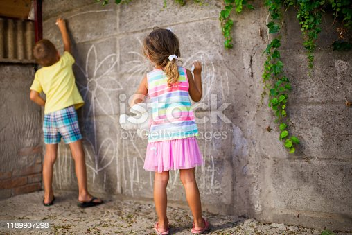 983418152 istock photo Cheerful little children having fun painting wall 1189907298