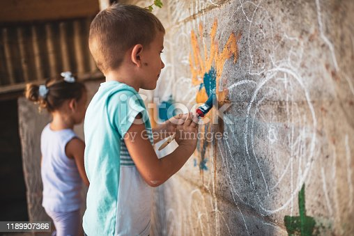 983418152 istock photo Cheerful little children having fun painting wall 1189907366