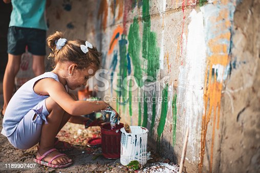 983418152 istock photo Cheerful little children having fun painting wall 1189907407