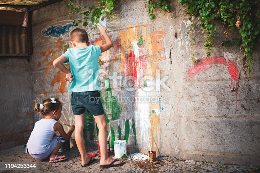 983418152 istock photo Cheerful little children having fun painting wall 1194253344