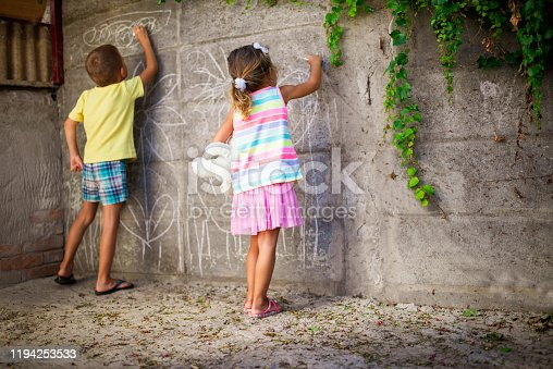 983418152 istock photo Cheerful little children having fun painting wall 1194253533