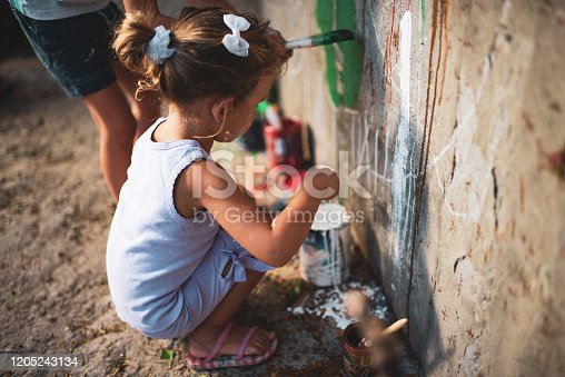 983418152 istock photo Cheerful little children having fun painting wall 1205243134