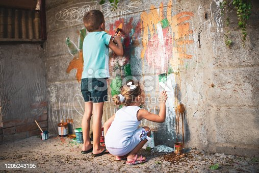 983418152 istock photo Cheerful little children having fun painting wall 1205243195