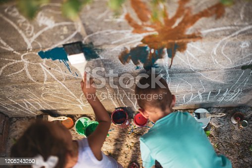 983418152 istock photo Cheerful little children having fun painting wall 1205243250