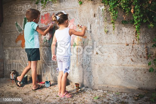 983418152 istock photo Cheerful little children having fun painting wall 1205243330