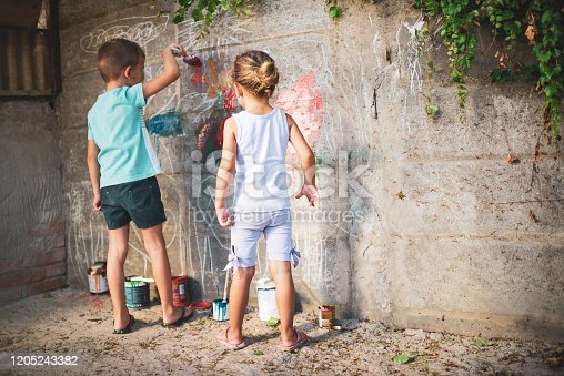 983418152 istock photo Cheerful little children having fun painting wall 1205243382