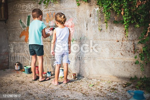 983418152 istock photo Cheerful little children having fun painting wall 1212922517