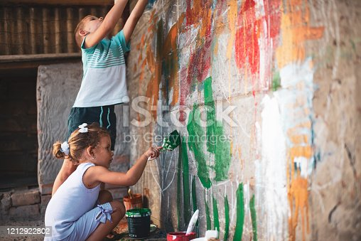 983418152 istock photo Cheerful little children having fun painting wall 1212922802