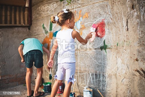 983418152 istock photo Cheerful little children having fun painting wall 1212922880