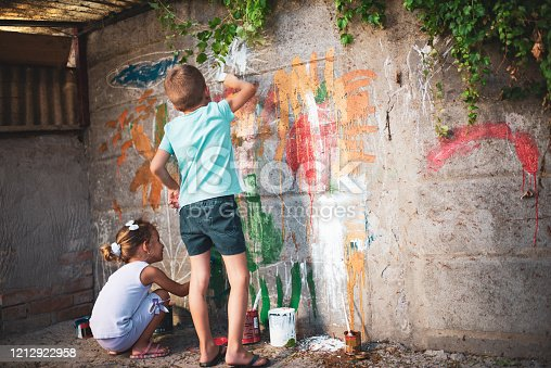 983418152 istock photo Cheerful little children having fun painting wall 1212922958