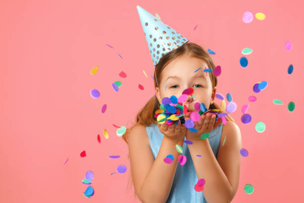 Cheerful little girl celebrates birthday. The child blows confetti from the hands. Closeup portrait on pink coral background. Cheerful little girl celebrates birthday. The child blows confetti from the hands. Closeup portrait on pink coral background. carnival children stock pictures, royalty-free photos & images