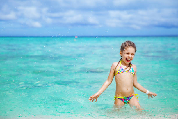 cheerful little girl enjoy the tropical sea - girl alone in swimsuit stock photos and pictures