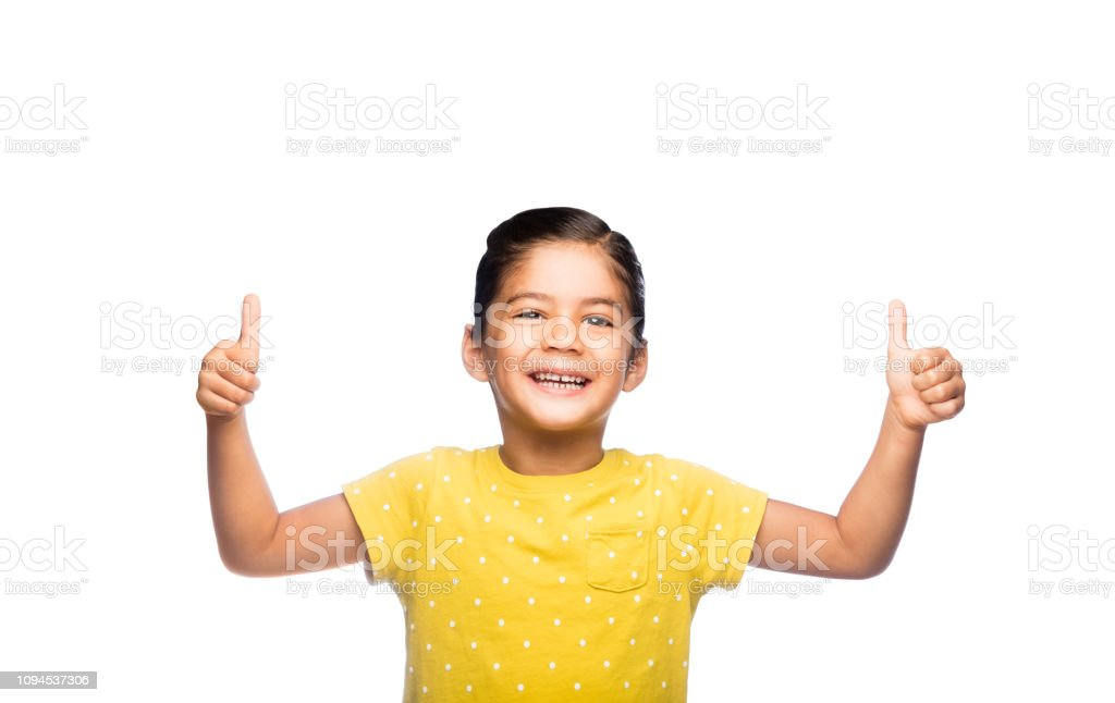Cheerful little girl giving thumbs up stock photo