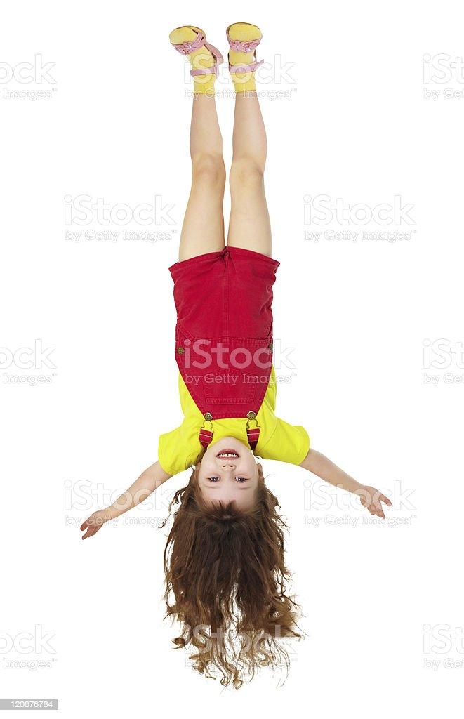 Cheerful little girl hangs upside down on white stock photo