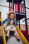 Happy little girl having fun and laughing while playing and sliding down playground slide