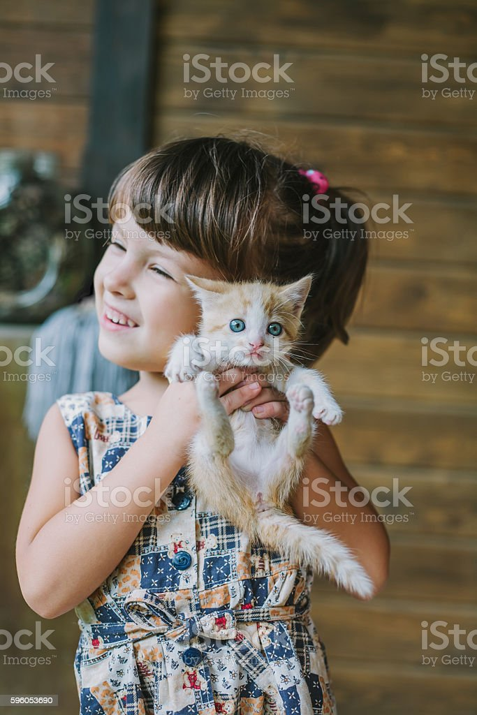 cheerful little girl holding a cat in her arms royalty-free stock photo