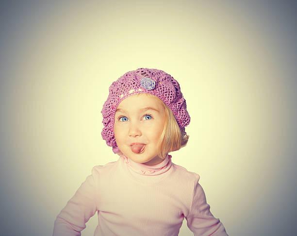 fröhliche kleine mädchen in einer baskenmütze zeigt sprache. - kindermütze häkeln stock-fotos und bilder