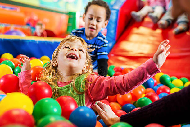 Cheerful little girl in playroom. stock photo