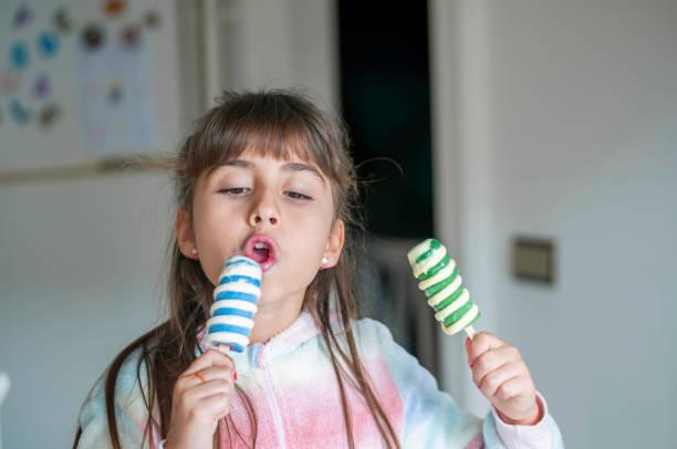 Fröhliches kleines Mädchen in der Küche mit Eis – Foto
