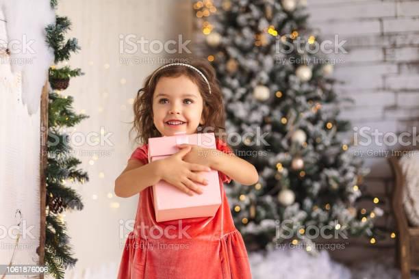 Cheerful little girl is hugging christmas gift on christmas tree picture id1061876006?b=1&k=6&m=1061876006&s=612x612&h=wv0zyug ukwcufhzpintovdhwnsgerrgfdmpklslqok=