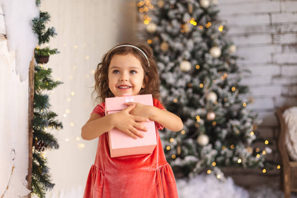 Cheerful little girl is hugging Christmas gift on Christmas tree Cheerful little girl is hugging Christmas gift on Christmas tree and lights background. baby girls stock pictures, royalty-free photos & images