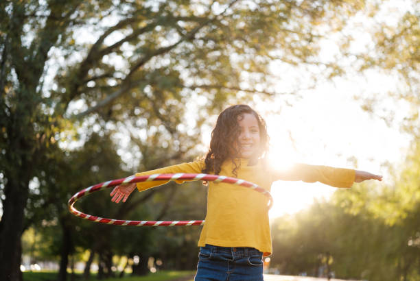 Cheerful little girl playing with a hula hoop stock photo