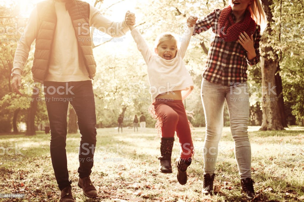Cheerful little girl playing with parents and enjoying together in park on sunny day. royalty-free stock photo