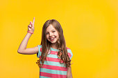Charming casual girl smiling at camera and pointing un on orange background.