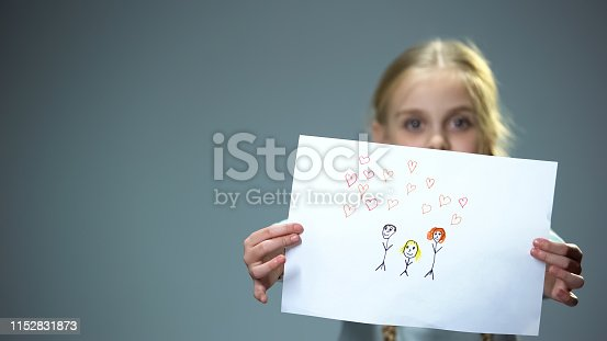 Cheerful little girl showing family picture into camera, feeling parental love