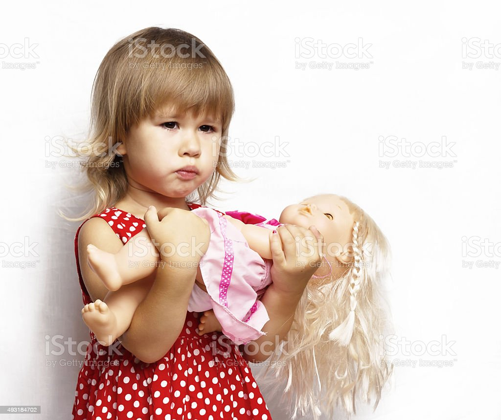 Cheerful little girl with a doll stock photo