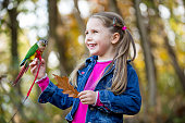 Cheerful Little Girl With Pet Parrot Sitting on her Hand Outdoors in Forest.