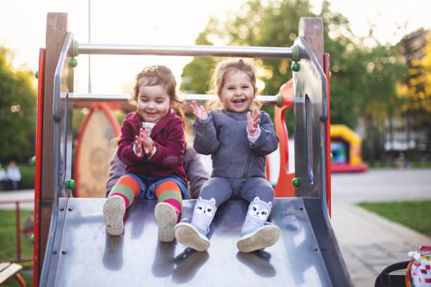 vrolijke kleine meisjes zittend op een glijbaan in de speeltuin - speeltuin stockfoto's en -beelden