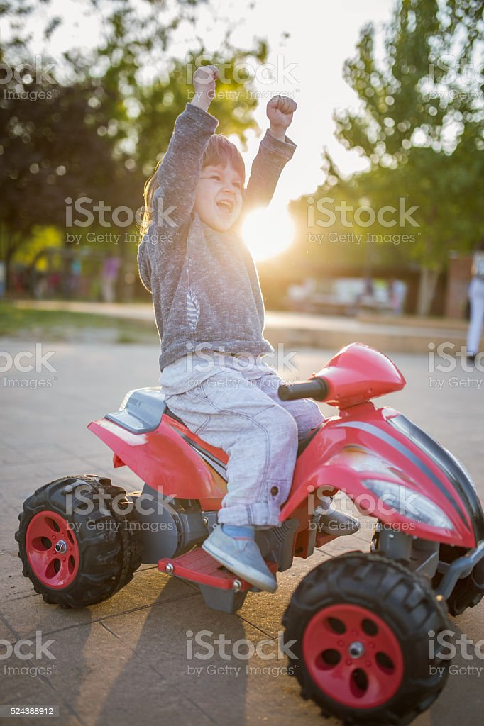 Cheerful Little Kid Celebrating Success On Toy Motorcycle Stock ...