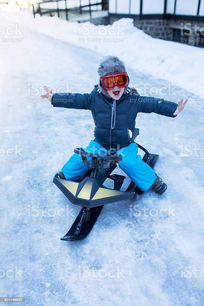 Cheerful little kid having fun on his snowmobile. foto stock royalty-free