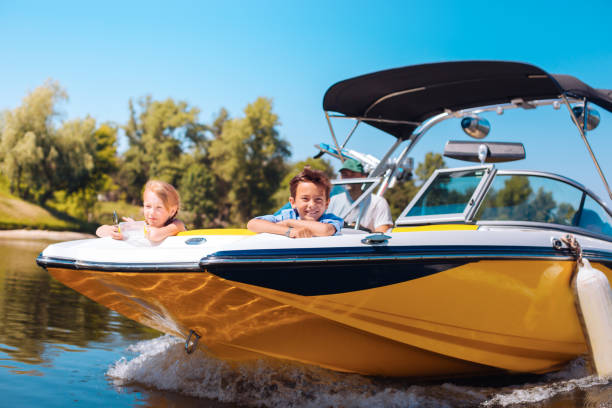 Cheerful little siblings enjoying view from boat bow stock photo