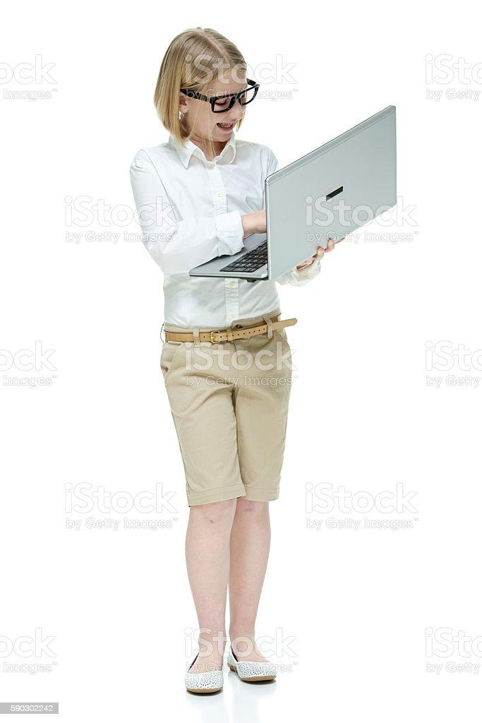 Cheerful little student working on laptop royaltyfri bildbanksbilder