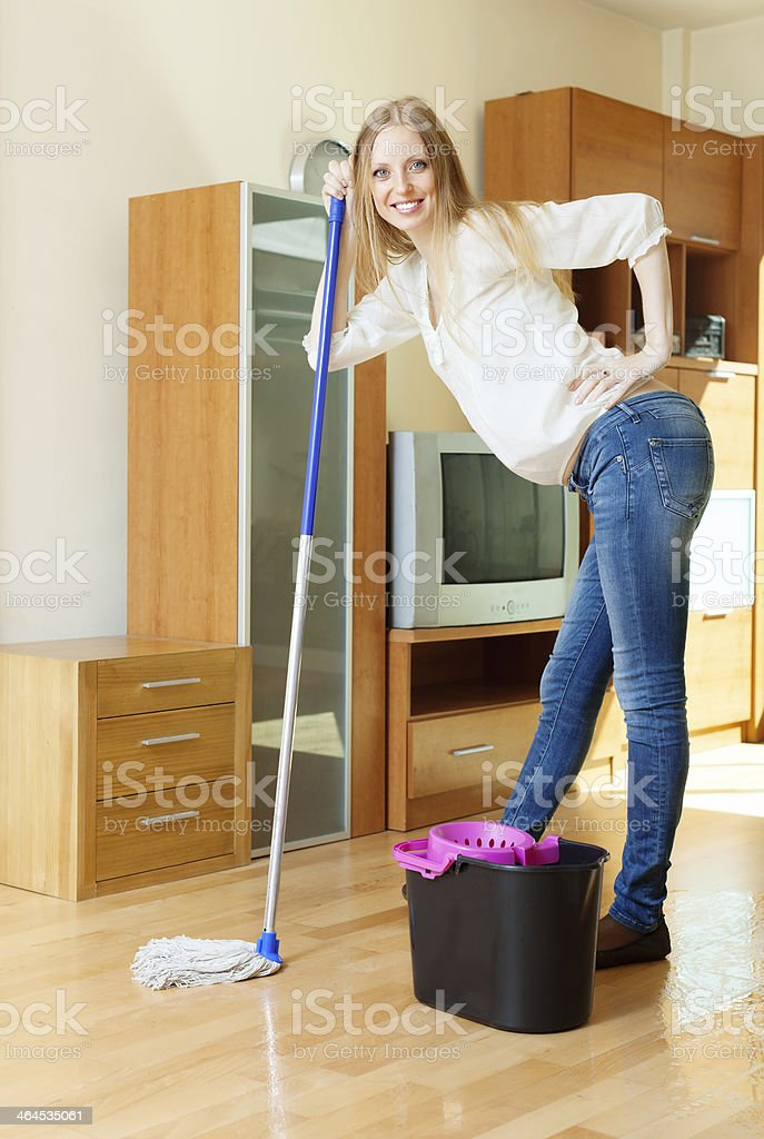 cheerful long-haired girl washing floor with mop stock photo