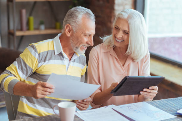Cheerful loving aged couple involved in paperwork at home stock photo