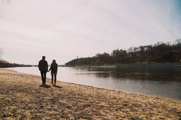 Cheerful loving each other couple kisses. Walk on the river bank and embrace stock photo
