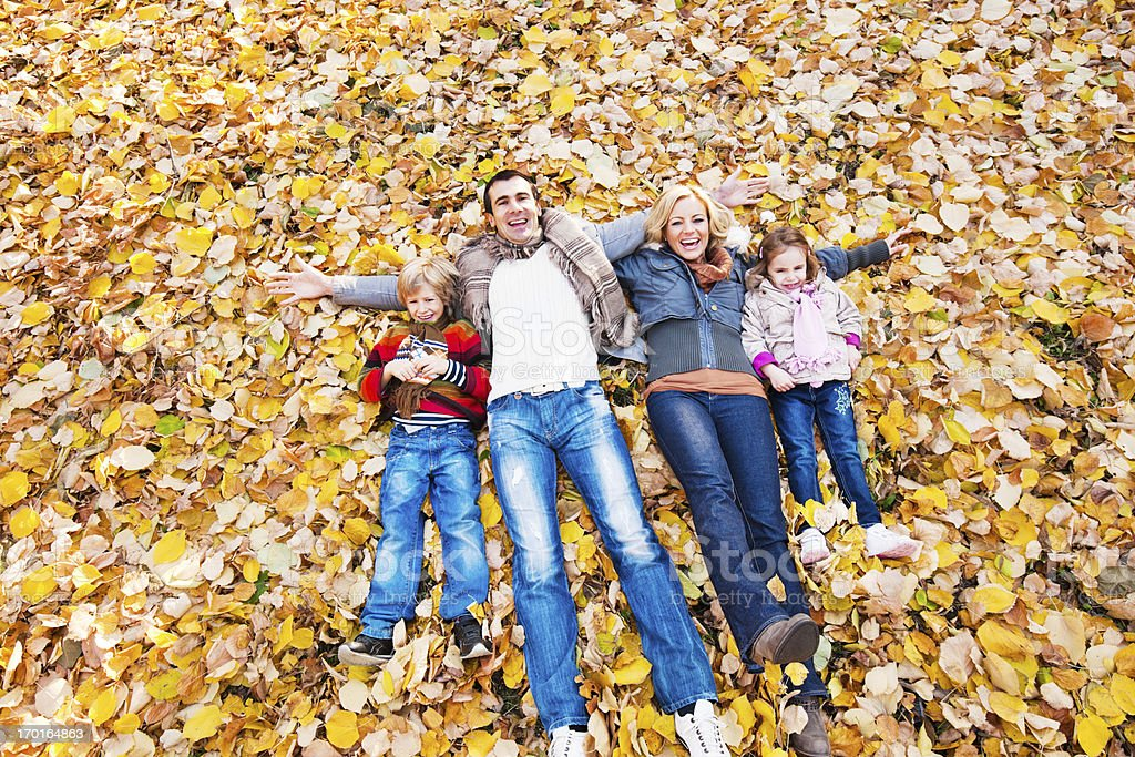 Cheerful loving family lying among leaves in park. royalty-free stock photo