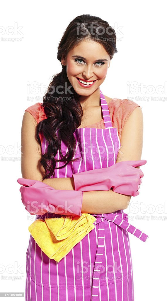 Cheerful maid Portrait of a happy young woman wearing an apron and washing up gloves, standing with crossed arms against white background and smiling at the camera. 20-24 Years Stock Photo