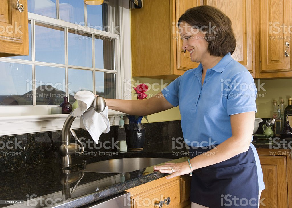 Cheerful Maid Polishing Kitchen Sink Faucet stock photo