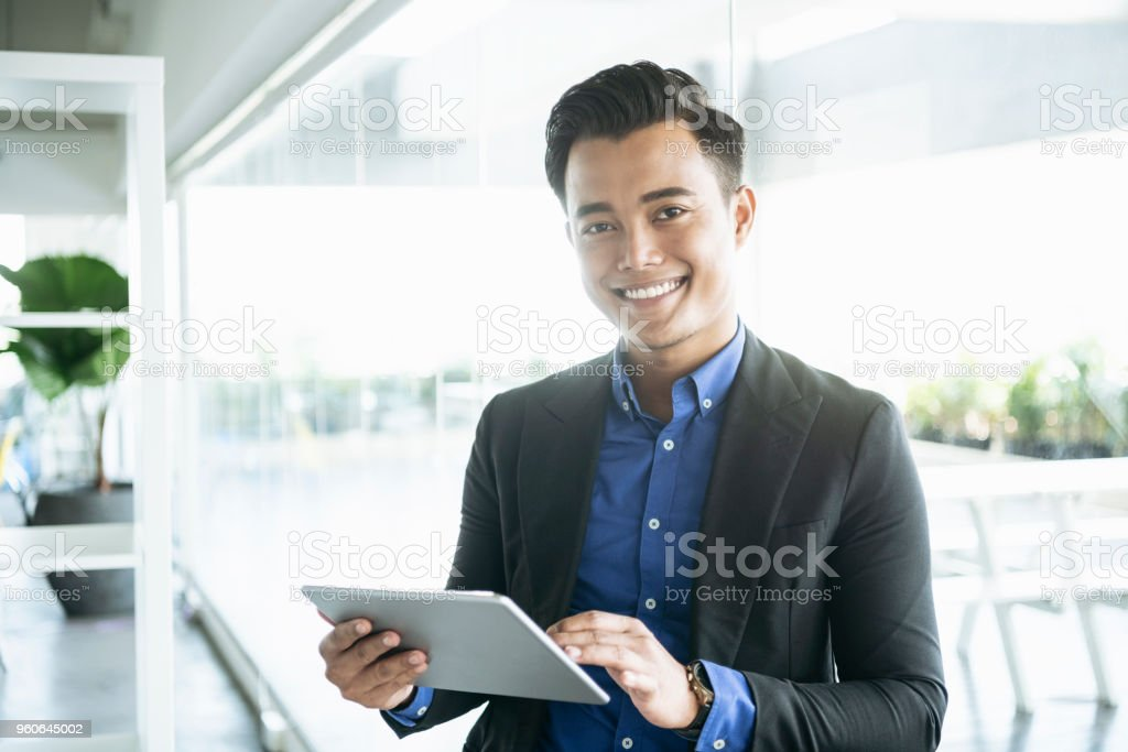 Cheerful Malaysian businessman with digital tablet stock photo