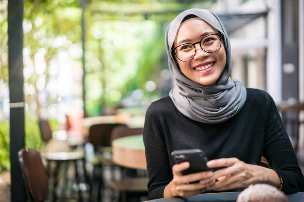 Cheerful Malaysian businesswoman in a cafe stock photo